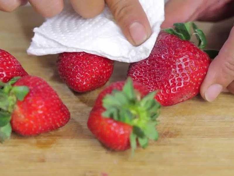 Sau khi rửa sạch, lau dâu tây bằng khăn giấy sẽ giúp loại bỏ hẵn bụi bẩn, mảng bám.