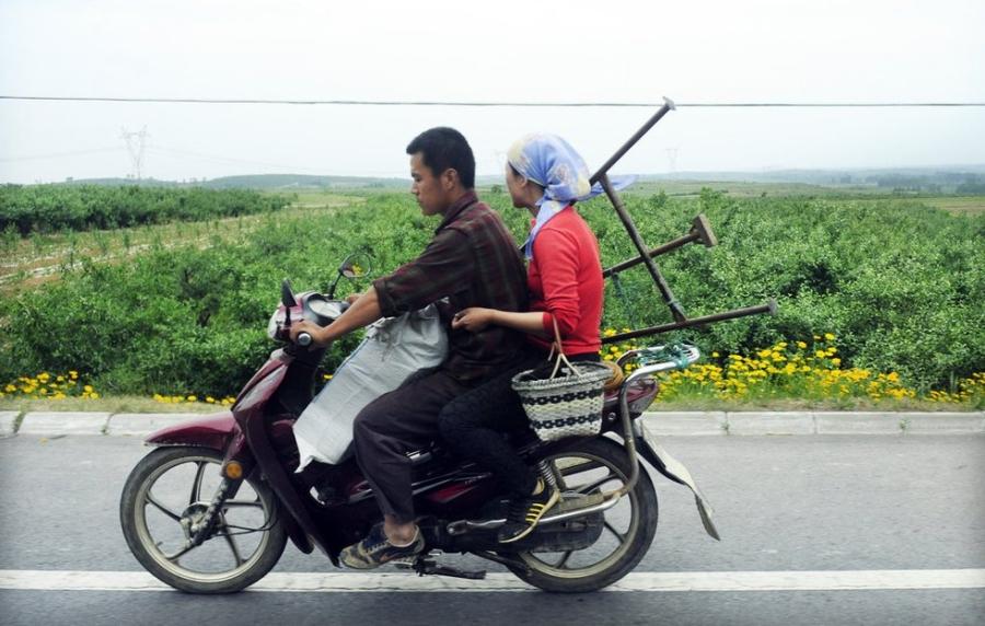 Một cặp vợ chồng nông dân Yên Đài mang theo cả bao tải lớn túi thuốc sâu ra ruộng táo.
